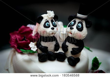 beautiful white wedding cake with figurines of animals close-up