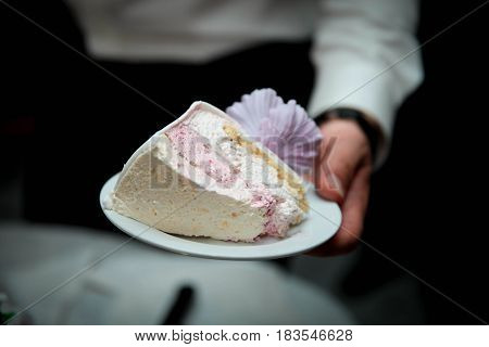 the groom holds the piece of white wedding cake