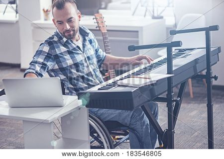 Recording my music session. Involved smiling smart invalid sitting in the wheelchair in the studio and enjoying musical therapy while playing the musical keyboard and using gadget for recording