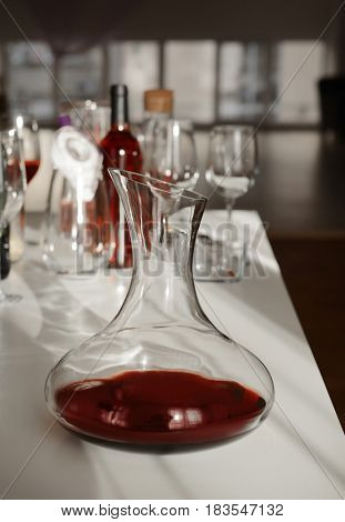 Decanter with red wine on table against blurred background