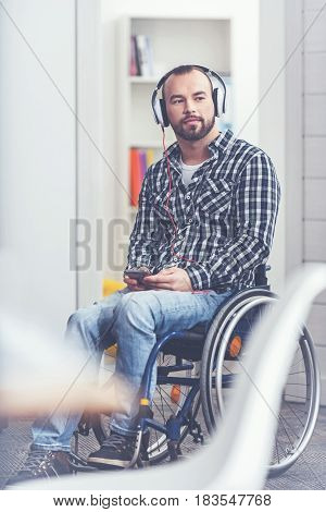 Spending every day with music. Involved handsome bearded man sitting on the wheelchair in the studio and using gadget and earphones while listening to the music