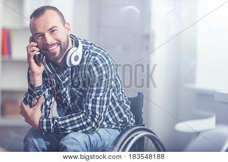 Full of joy. Kind bearded pleasant invalid sitting on the wheelchair at home and using modern devices while enjoying conversation on the phone