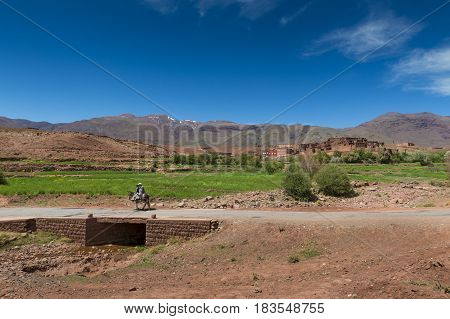 Telouet Morocco - April 14 2016: Father and son riding a donkey in the outskirts of the town of Telouet in the High Atlas region in Morocco.
