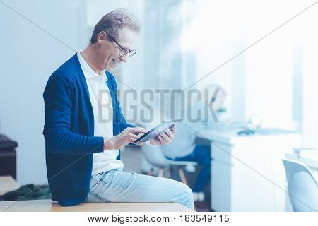 Life online. Cheerful handsome man sitting on the table and using laptop while working in the office