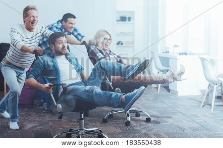 So much fun. Cheerful delighted colleagues sitting in the swivel chairs and having fun while enjoying the break
