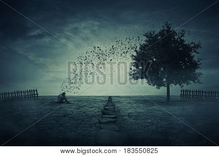 Young man sit alone on the cracked ground in the middle of his farm garden in front of a magic tree that cast its leaves in the wind. Energy changing concept between people and nature.