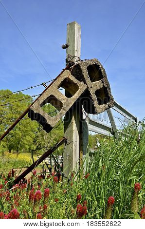 Several building blocks hang from a corner post of a fence surround with flowers blooming and long grass.