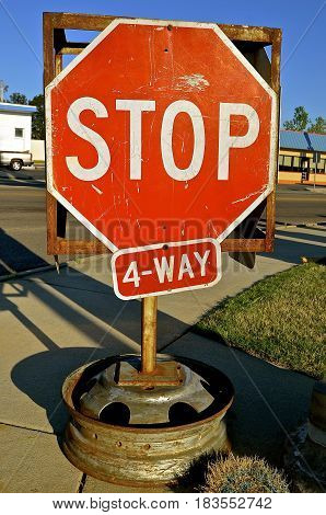A portable 4-Way stop sign stands on a sidewalk corner of a street intersection with a car rim as a base.