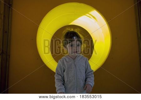 Cute little girl crawling through tube tunnel slide on children's playground