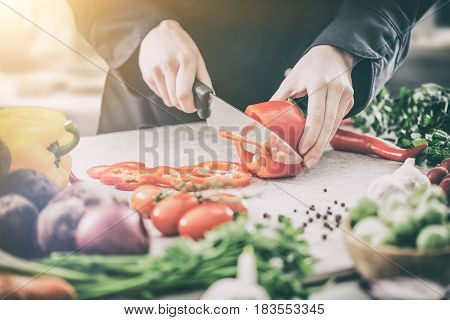 The chef prepares the meal, cuts pepper with a chef's knife.