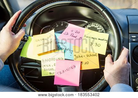 Sticky notes sticker on the steering wheel. Multitasking concept.