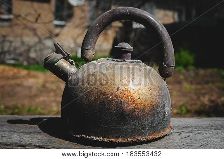 Old dusty teapot in a wooden background
