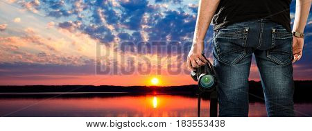 Photographer looks at lake and forest landscape at sunset.