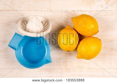 Flat Lay Above Three Lemons And Plastic Strainer