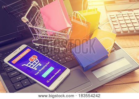 Smart device and online shopping app with 5 items in a cart / basket. Online shopping saves an individual the hassle of searching several stores and the waiting in long queues to buy particular items.