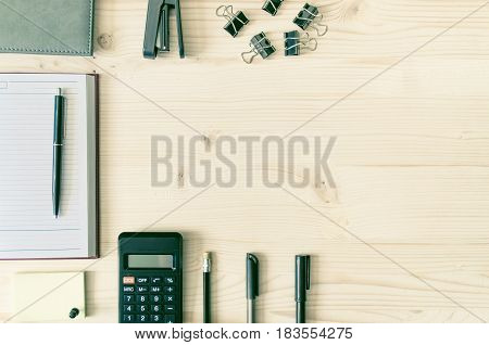 Office desk table with book planner pen calculator wallet pencil ruler stapler paper clips clamps sharpener on right. Top view with copy space flat lay. Business background.