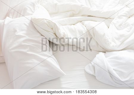 Top view of an unmade bed after waking up in the morning. White pillows, a blanket and a shower towel are on the bed.
