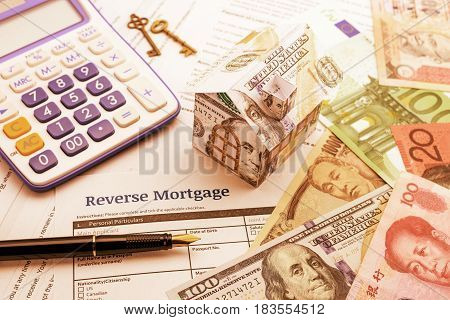 Vintage / retro color style : Fountain pen, brass keys, a calculator, a dollar paper house and a blank reverse mortgage form with banknotes of most dominant countries in the world on a table.