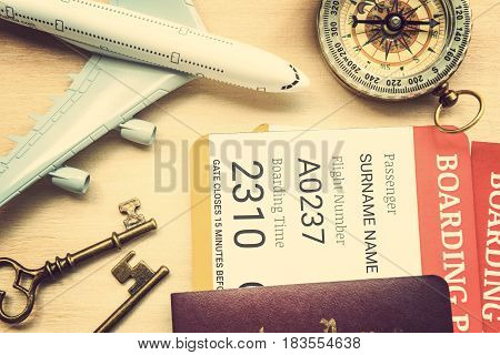 Retro color style : Two boarding passes with passports, vintage brass keys, a compass, a white model airplane on a table. Holidays travelling with a family to the most top destinations concept.