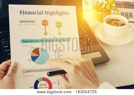 Chief financial officer or CFO holds, sees and analyses financial highlights on his table. Financial highlights include charts of total sales revenue and sales revenue breakdown by geography or region