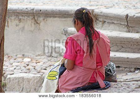 Mujer artesana bordando para ganarse la vida