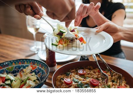 Closeup of people putting food on the plate and having dinner together