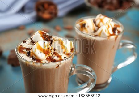 Glass cups of cocoa with marshmallows and syrup, close up