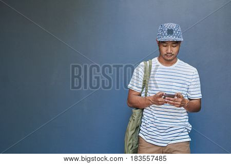 Stylishly dressed young Asian man sending text messages on his cellphone while standing against a gray wall outside