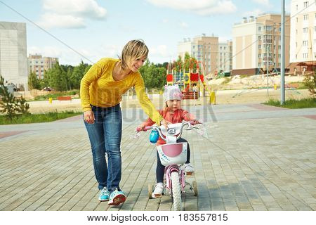 little girl with mother riding a bicycle. child outdoor