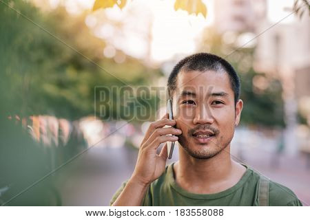Portrait of a casually dressed young Asian man smiling while standing outside on a city street talking on a cellphone