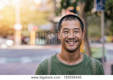 Portrait of a casually dressed handsome young Asian man smiling while standing alone outside on a city street on a sunny day