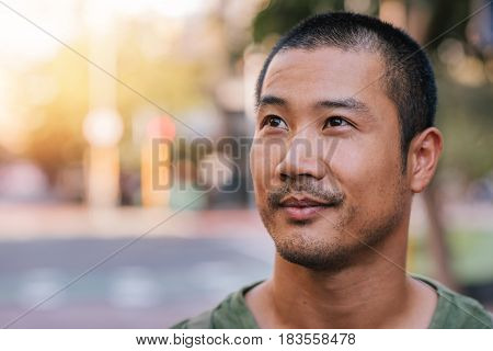 Casually dressed handsome young Asian man looking up and smiling while standing alone outside on a city street on a sunny day