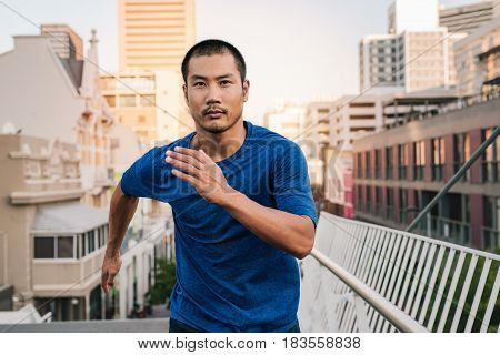 Athletic young Asian man in sportswear looking focused crossing over a bridge while out for a run through the city