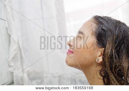 headshot young woman showering, hispanic interior shot