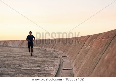 Focused and fit young Asian man in sportswear running alone along a boardwalk outside in the early morning