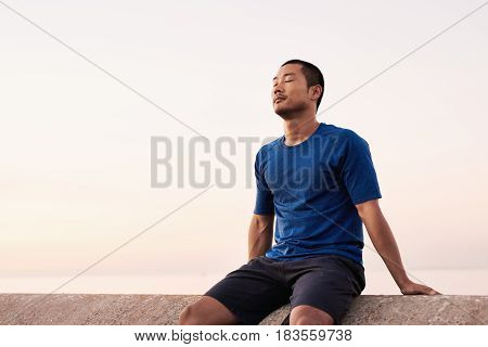Fit young Asian man in sportswear sitting with his eyes closed on a ledge while taking a break from an early morning run