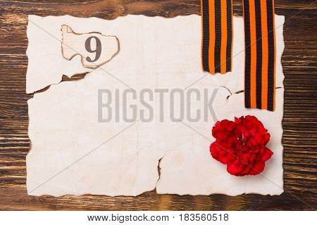 A burnt sheet of paper on the table with a red carnation and a number 9 and two St. George ribbons