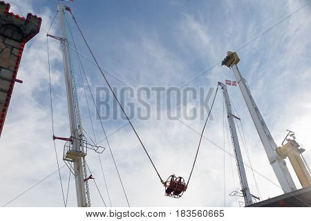 In a fairground a manege which allows to throw itself very high at the end of an elastic