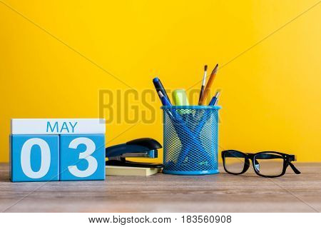 May 3rd. Day 3 of month, calendar on business office table, workplace at yellow background. Spring time.