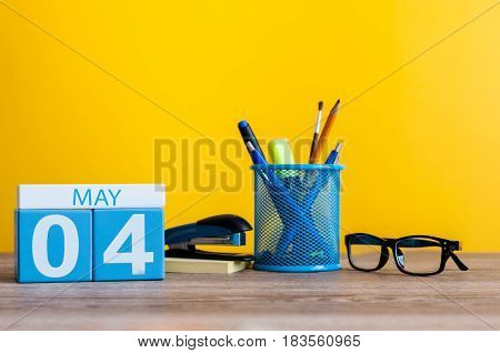 May 4th. Day 4 of month, calendar on business office table, workplace at yellow background. Spring time.