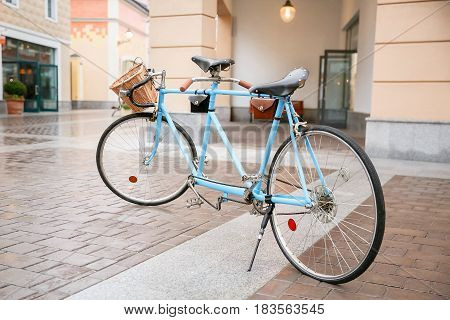 Blue bicycle on the street in the background of shops