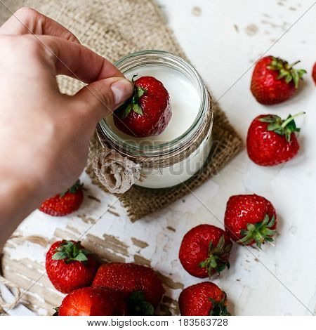 Hand Putting  Strawberry In  Yogurt