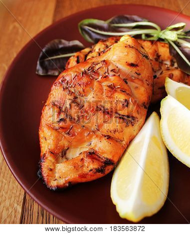 Grilled chicken breast served on plate with lemon. Wooden background .