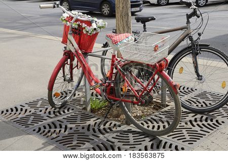 GRAZ, AUSTRIA - MARCH 20, 2017: Red bicycle parked nex to a tree at the streets of Graz the capital of federal state of Styria Austria.