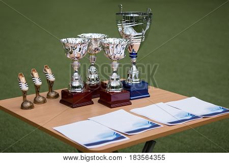 Cups and rewards on table, background of a football field
