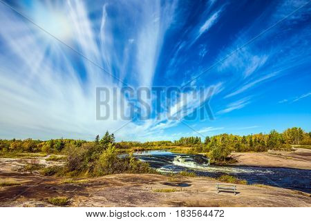 The concept of recreational and ecological tourism. Indian summer in Manitoba, Canada. Improbable plumose clouds and autumn sun over the river Winnipeg