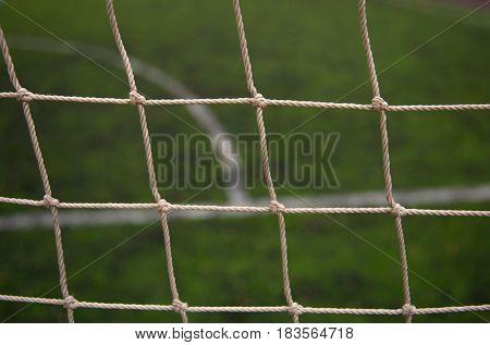 Football field. Green synthetic grass. Net grid closeup