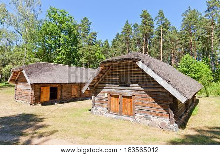 RIGA LATVIA - JUNE 13 2016: Wooden horseshoe shaped laborer outbuilding (circa 1780s) of Poki farmstead of Zemgale ethnic group. Exhibited in Ethnographic Open-Air Museum of Latvia since 1936