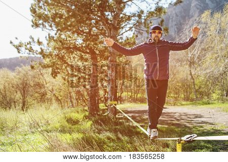 A man, aged with a beard and wearing sunglasses, balances on a slackline in the open air between two trees at sunset on background blue sky
