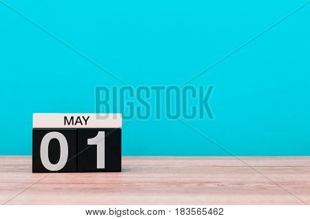 May 1st. Image of may 1 wooden color calendar on turquoise background. Spring day, empty space for text. International Workers' Day.
